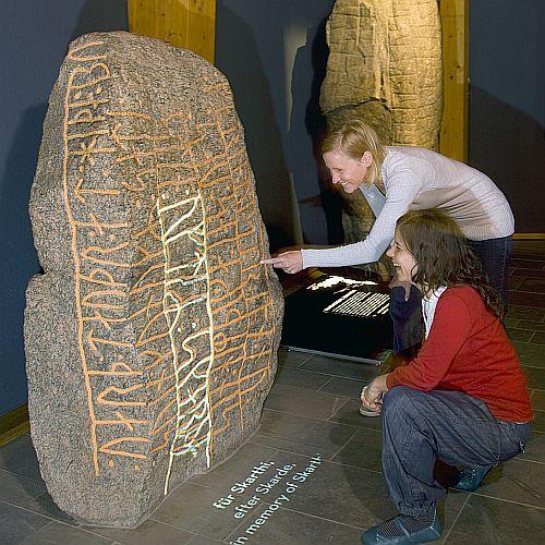 Besucher vor einem Runenstein im Wikinger Museum Haithabu