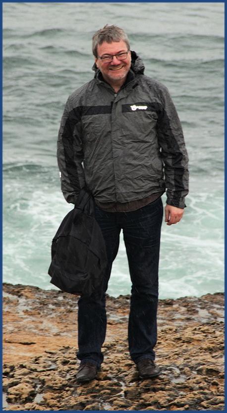 Foto von mir. Ich stehe in Ericeira direkt am Meer ... aber im Regen.