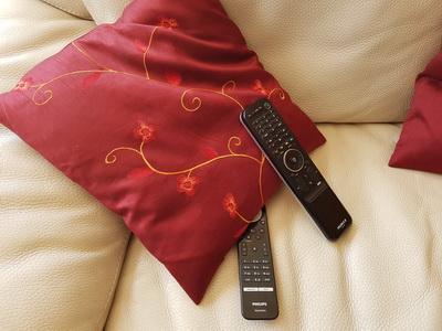 Zwei Fernbedienungen und ein Kissen auf einem Sofa