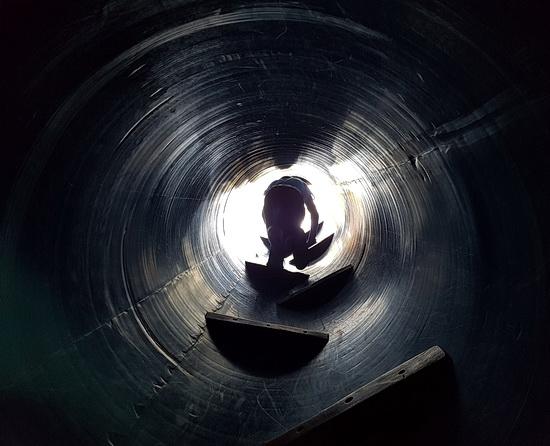 Jemand klettert durch eine enge Metallröhre